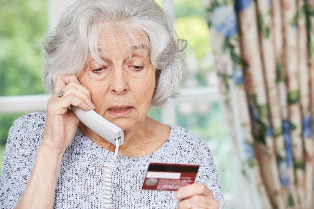 Ältere Dame telefoniert mit ihrer Kreditkarte in der Hand